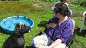 "Gadget, with gray, very close-cropped hair, sits with his tongue hanging out, looking at Sharon. He has a tiara of curled ribbons of many colors on his head, with a big bow in the middle. Behind him is a blue kiddie swimming pool, filled with water. Sharon sits in her powerchair with black sunglasses on, one hand holding a cake in her lap that says, ""Happy Birthday Gadget"" in peanut butter and biscuits on white icing. With the other hand she is gesturing to herself as she talks to Gadget. In the background is a green lawn and people in lawn chairs."