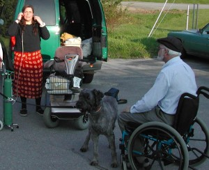 Sharon is standing in a parking lot, adjusting the tubing on her oxygen cannula. Next to her is her large, 4-wheeled mobility scooter. In the foreground of the picture is Norm, sitting in a lightweight wheelchair with an electric blue frame. He is facing mostly away, so we see his side, back and profile. Hes wearing a tweed cap and glasses, and has a white fringe of hair under the cap and white beard. Sharon is wearing a very bright, lively red wraparound skirt with yellow flowers and a black, long-sleeved top. Her dark hair is very long, swept to the front. Between Norm and Sharon stands a young, distracted Gadget, in a summer haircut. He is not wearing any gear, just a rainbow collar and a black leash. He is standing splay-legged, looking into the distance.