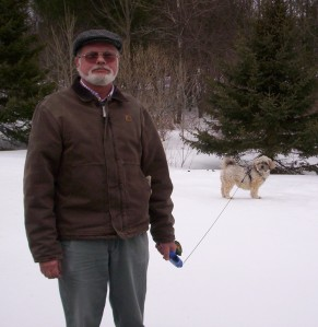 A ruddy-faced man of white/Native heritage stands in the snow with a small dog on a flexi-lead. The man wears a tweed cap, tinted glasses, a brown carhart jacket, and gray baggy pants. He has a white beard and mustache and stands a little stiffly, his hands curled under, a stoic expression on his face. The dog is a Havanese, about 12 pounds, with curly white hair. She is stairing at Norm quizzically. They are surrounded by smooth snow, a lawn presumably, and in the distance behind are evergreens and treeless deciduous trees.