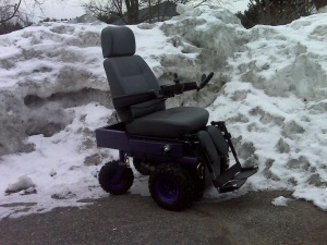 Purple powerchair sits in front of six-foot mountain of snow