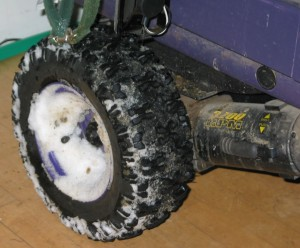 Left purple powerchair wheel and motor, with snow slush