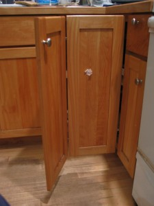 An open, wood, corner cabinet door. There are two panels with a hinge connecting them. There is a chrome knob on the upper, outer corner -- on the left -- and a piece of pink paper is stuck in the middle of the other panel.