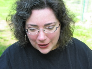 Sharon with her head titled down, mouth open, talking. She has wavy salt and pepper hair, a rosey complexion, wire-frame pink glasses with rhinestones at the corners, and is wearing dark red lipgloss and dark purple eye shadow.