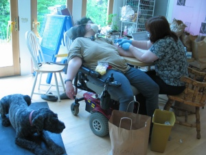 Barnum lies on a black yoga mat next to Sharon, who is in her powerchair with the back reclined all the way and her feet slid off the footplate. She's wearing a large white mask covering all of her face but from her eyes up. One arm is hanging over the side of the armrest, the other is outstretched on the table where a nurse in a medical mask and gloves is changing Sharon's PICC line dressing.