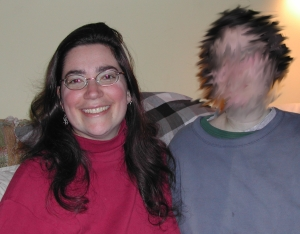 Sharon ten years ago, with very long, dark hair, and a big smile, sitting on a couch next to a person in a blue sweatshirt whose face is blurred out.