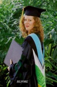 Tall woman with long wavy red hair smiles at the camera in a black mortar board cap and black gown with green, white, and blue robe indicating advanced degree and holding a black folder presumably containing her diplomas.