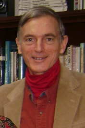Ralph in 2011. His hair is shorter and mostly gray. He is much thinner and is wearing a sport coat with a kerchief around his neck. He is standing in front of a bookcase. His smile and eyes look much more alive than in the earlier picture.