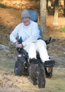 Sharon in a woodsy setting in her large outdoor chair. It has very large black knobby tires, elevated black metal leg rests, a purple square base, and an oversized gray captain's chair with headrest.. Sharon is reaching into a treat pouch hanging from the joystick while baby Barnum (4 months old) trots toward her.  He is shorter than the wheels. The chair gives an impression of great size and power.