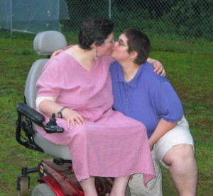 Sharon wearing a long pink dress sitting in her powerchair on the lawn with Betsy kneeling on one knee beside her. They are facing each other and kissing. Sharon has her arm around Betsy. Betsy is wearing a blue polo shirt and white shorts. Both women have short, dark hair, glasses, and a few extra pounds.