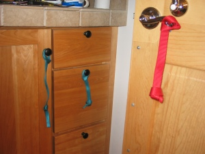 A door with a metal door lever with a red nylon webbing pull attached. It has a knot in the bottom. Next to the door is a cupboard, with a cabinet door and three drawers. Thin, turquoise nylon pulls hang from the cabinet doorknob and the knob of one of the drawers.