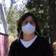 A white woman with shoulder-length brown hair stands outside wearing a large white cotton mask that covers her nose and the bottom half of her face.
