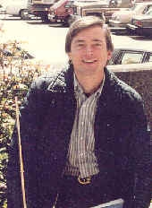 A white man who looks to be in his early thirties, with straight brown hair parted on teh side, wearing a blue windbreaker. He is smiling and appears to be standing in front of or next to his car.