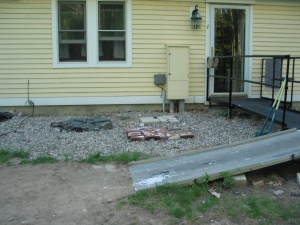 Doorway and part of exterior wall of yellow wood-shingled house. A metal ramp meets the door, with a second ramp at a right angle down to the lawn. The ground is bare dirt at the bottom of the ramp. Behind it, next to the house, the ground is covered with gravel. There are three toileting areas, about three feet square each, one of pieces of asphalt, one of bricks, and one of four cement pavers. If you look closely, you see a dog poop on the cement pavers.