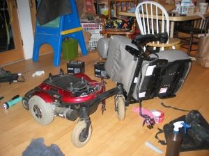 The seat of the powerchair sits sideways on the floor, disconnected from the base. Around it are tools, hardware, rags, cleaning solution, a flashlight, and other debris.
