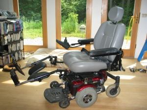 Side view of the powerchair with long, black, metal leg rests and a gray seatbelt with a red buckle.