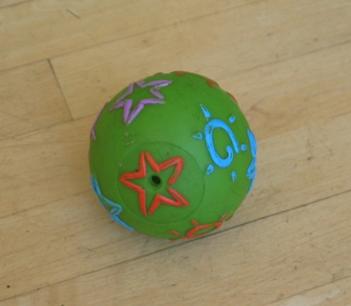 "Green plastic ball with blue, orange, and pink slightly raised designs on it. The designs are five-pointed stars or ""suns"" -- rough-shaped circles with little lines around them like rays. This ball is scuffed up quite a bit."