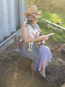 A light-skinned woman with gray hair wearing a straw hat and summer-weight lilac dress sits on a tree stump holding a baby goat pressed to herself. The goat is mostly white with a brown and black head. It is the size of a large cat. The sun is shining, and Connie is smiling widely.