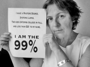 "Black and white picture of a middle-aged white woman with short dirty-blond hair. She is wearing a white, sleeveless shirt and holding up a sign that says, ""I have a Master's Degree, Systemic Lupus, Two Kids Entering College in Fall, and Less than $20 to my Name. I am the 99%."