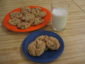 An orange Fiesta-ware dinner plate with 8 cookies behind a blue Fiesta-ware saucer with 3 cookies. A glass of white liquid sis next to them on a pale wood surface.