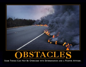 "A poster showing a paved road with a huge, long boiling mass of molten lava pouring out across the road, black smoke billowing up from it. Under the picture in large orange letters, it says, ""Obstacles."" Beneath that in smaller type, it says, ""Some things cannot be overcome with determination and a positive attitude."""