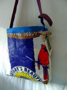 Colorful tote bag made from bird seed bags, includes a bright red cardinal sitting on a branch, and a sunflower at the base of the bag.