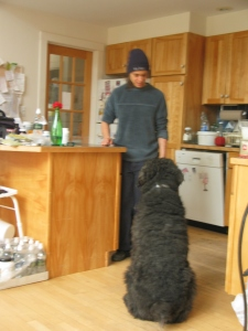 Barnum sits staring fixedly at a young woman standing in the kitchen.