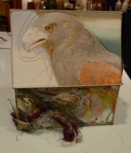 Top of treasure box has head and shoulders of a brown hawk with red wings. There are feathers on teh side of the box.