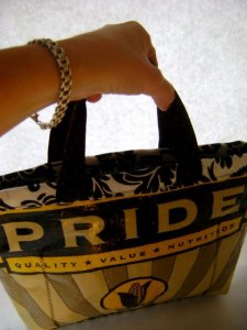 Tote bag in black and yellow that says Pride in big yellow letters on a black background.