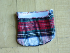 Back of a red plaid flannel pouch with strip of white Velcro sewn across the top.