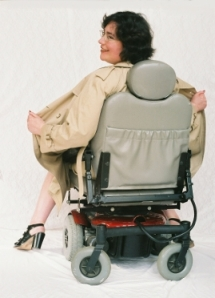 Sharon sits in her powerchair, which is backwards; both Sharon and the chair are facing away from the camera. The chair has a gray seat and wheels, with a cherry-red base. Sharon wears a tan trench-coat, and she is holding it open on both sides, as if she is flashing whoever is in front of her. All that can be seen of Sharon are her naked calves, her feet in four-inch-high patent-leather heels, her hands pulling open the trench-coat, and her head. She is turning her head toward the camera, so her face is in profile, smiling mischievously. Her facial expression is saucy, letting you know that she does not take herself too seriously.