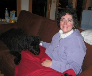 Gadget lying on his front on a brown couch, his chin resting on a red quilt on Sharons knee. Sharon -- bundled in a turtleneck and hoodie -- has her hand on Gadgets neck and is smiling a little fixedly toward the camera.