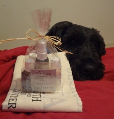 Clear cellophane bag tied with a straw bow with many small bottles in it, sitting on a folded tote bag. Barnum rests his chin on the bed just behind the items.